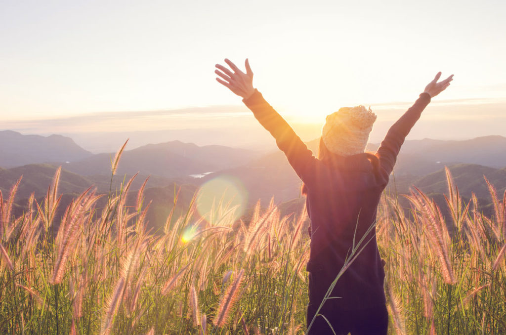 Lady standing in a field of long grass with the sun setting in front of her and her arms spread out in a star shape. SHe is over looking the countryside.
